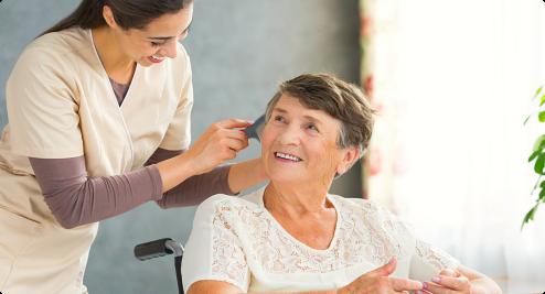 caregiver combing senior woman