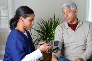 caregiver checking blood pressure
