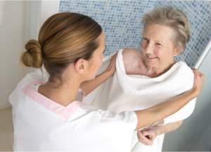 caregiver assisting senior woman in the bathroom
