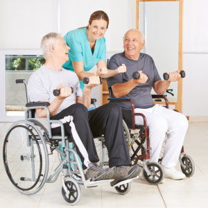 caregiver assisting two senior man in exercising