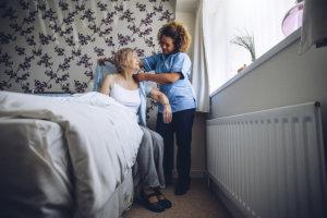 caregiver assisting senior woman in dressing